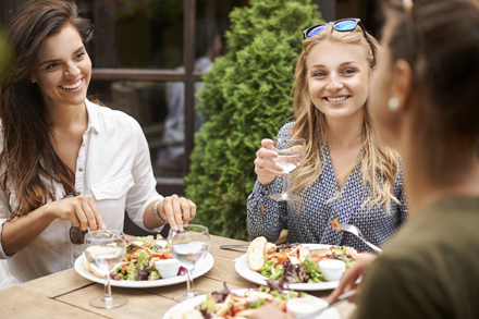 a group of women eating together at a restaurant