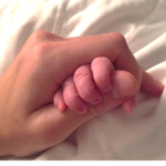 picture of a woman holding a babies hand