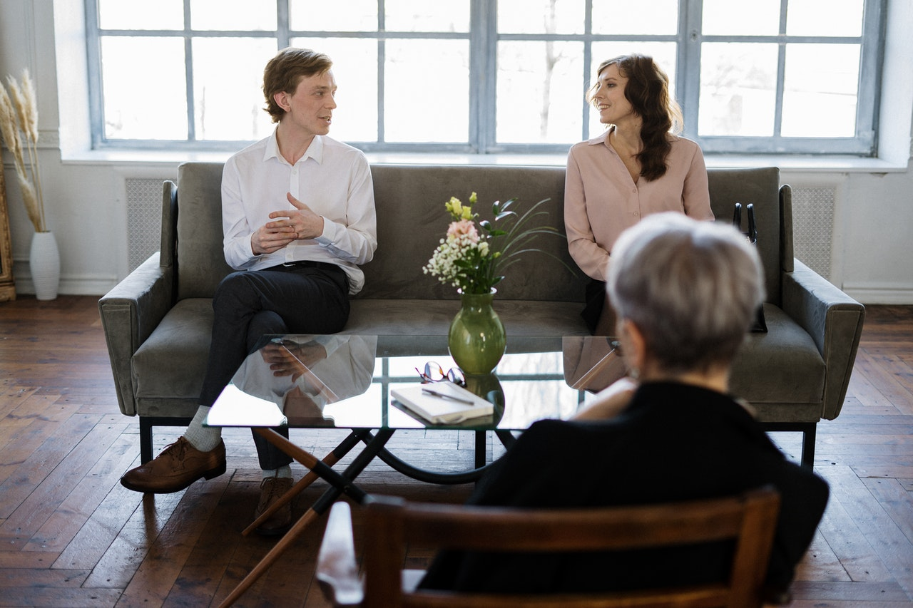 Couple sitting on a couch talking to therapist